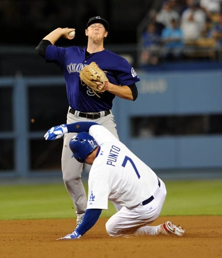 Jul 12, 2013; Los Angeles, CA, USA;  Colorado Rockies second baseman DJ LeMahieu (9) throws to first as Los Angeles Dodgers second baseman Nick Punto (7) is out on a double play in the eighth inning at Dodger Stadium. Rockies won 3-0. Mandatory Credit: Jayne Kamin-Oncea-USA TODAY Sports