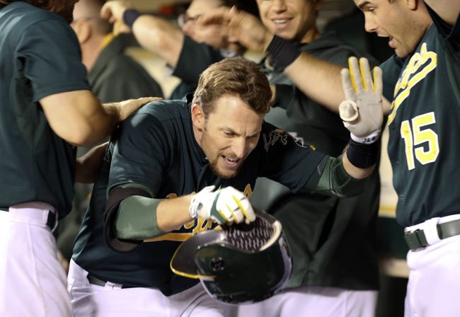 Jul 12, 2013; Oakland, CA, USA; Oakland Athletics shortstop Jed Lowrie (8) walks through a tunnel of players after hitting a solo home run against the Boston Red Sox during the sixth inning at O.co Coliseum. Mandatory Credit: Kelley L Cox-USA TODAY Sports