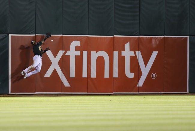 Jul 12, 2013; Oakland, CA, USA; Oakland Athletics left fielder Yoenis Cespedes (52) is unable to catch the ball along the wall against the Boston Red Sox during the ninth inning at O.co Coliseum. Mandatory Credit: Kelley L Cox-USA TODAY Sports