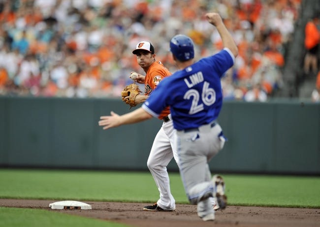 Jul 13, 2013; Baltimore, MD, USA; Toronto Blue Jays designated hitter Adam Lind (26) is out at second base as Baltimore Orioles shortstop J.J. Hardy (2) starts the double play in the first inning at Oriole Park at Camden Yards. Mandatory Credit: Joy R. Absalon-USA TODAY Sports