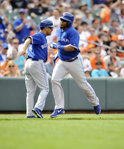 Jul 13, 2013; Baltimore, MD, USA; Toronto Blue Jays first baseman Edwin Encarnacion (10) is congratulated by third base coach Luis Rivera (2) after hitting a two-run home run in the first inning against the Baltimore Orioles at Oriole Park at Camden Yards. Mandatory Credit: Joy R. Absalon-USA TODAY Sports