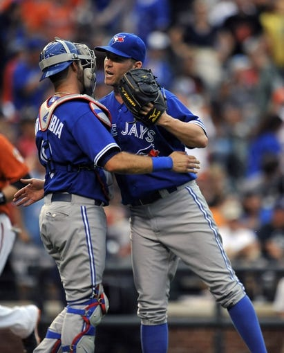Jul 13, 2013; Baltimore, MD, USA; Toronto Blue Jays catcher J.P. Arencibia (9) congratulates pitcher Casey Janssen (44) after a game against the Baltimore Orioles at Oriole Park at Camden Yards. The Blue Jays defeated the Orioles 7-3. Mandatory Credit: Joy R. Absalon-USA TODAY Sports