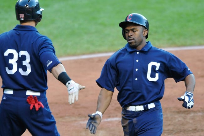 Jul 13, 2013; Cleveland, OH, USA; Cleveland Indians center fielder Michael Bourn (right) is congratulated by Cleveland Indians right fielder Nick Swisher (33) after scoring on a sacrifice fly ball in the third inning against the Kansas City Royals at Progressive Field. Mandatory Credit: David Richard-USA TODAY Sports