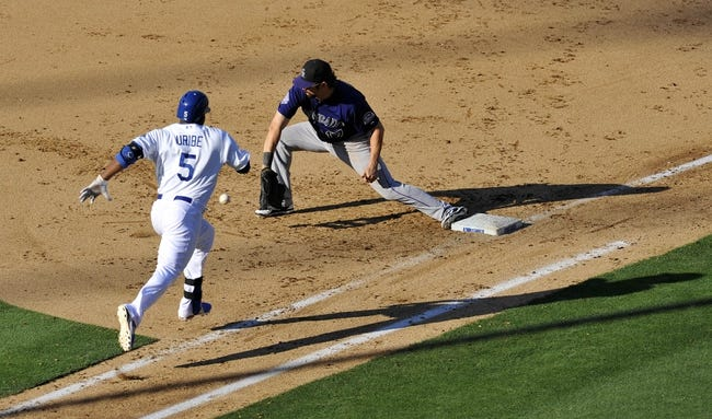 July 13, 2013; Los Angeles, CA, USA; Colorado Rockies first baseman Todd Helton (17) catches the ball from third to force out Los Angeles Dodgers third baseman Juan Uribe (5) during the seventh inning at Dodger Stadium. Mandatory Credit: Gary A. Vasquez-USA TODAY Sports