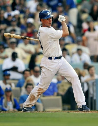 July 13, 2013; Los Angeles, CA, USA; Los Angeles Dodgers second baseman Mark Ellis (14) hits a single during the ninth inning against the Colorado Rockies at Dodger Stadium. Mandatory Credit: Gary A. Vasquez-USA TODAY Sports