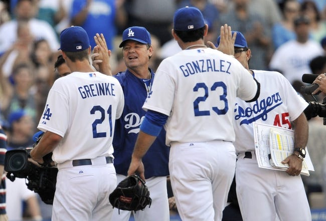July 13, 2013; Los Angeles, CA, USA; Los Angeles Dodgers pitching coach Rick Honeycutt (40) congratulates starting pitcher Zack Greinke (21) on his 1-0 complete game victory against the Colorado Rockies at Dodger Stadium. Mandatory Credit: Gary A. Vasquez-USA TODAY Sports