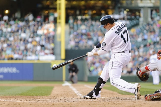 Jul 13, 2013; Seattle, WA, USA; Seattle Mariners first baseman Justin Smoak (17) hits the ball during the game against the Los Angeles Angels at Safeco Field. Seattle defeated Los Angeles 6-0. Mandatory Credit: Steven Bisig-USA TODAY Sports
