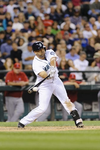 Jul 13, 2013; Seattle, WA, USA; Seattle Mariners designated hitter Kendrys Morales (8) hits the ball during the game against the Los Angeles Angels at Safeco Field. Seattle defeated Los Angeles 6-0. Mandatory Credit: Steven Bisig-USA TODAY Sports