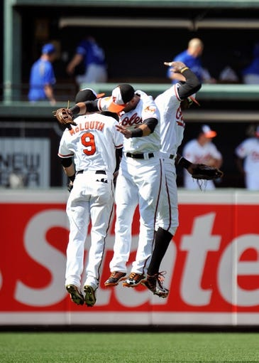 Jul 14, 2013; Baltimore, MD, USA; Baltimore Orioles outfielders Nate McLouth (left) Nick Markakis (center) and Adam Jones (right) celebrate after a game against the Toronto Blue Jays at Oriole Park at Camden Yards. The Orioles defeated the Blue Jays 7-4. Mandatory Credit: Joy R. Absalon-USA TODAY Sports