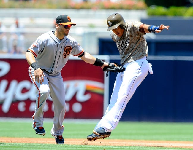 Jul 14, 2013; San Diego, CA, USA; San Diego Padres shortstop Everth Cabrera (2) is tagged out by San Francisco Giants second baseman Marco Scutaro (19) after a rundown during the first inning at Petco Park. Mandatory Credit: Christopher Hanewinckel-USA TODAY Sports
