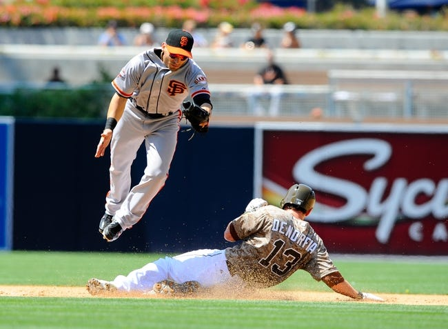 Jul 14, 2013; San Diego, CA, USA; San Diego Padres right fielder Chris Denorfia (13) slides safely into second base after a ball is thrown past San Francisco Giants second baseman Marco Scutaro (19) during the fourth inning at Petco Park. Mandatory Credit: Christopher Hanewinckel-USA TODAY Sports