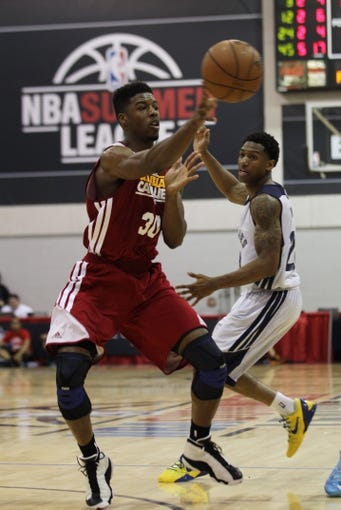 Jul 14, 2013; Las Vegas, NV, USA; Cleveland Cavaliers guard Carrick Felix passes the ball to a teammate as Memphis Grizzlies guard Gerald Robinson runs behind the play during an NBA Summer League game at Cox Pavillion. Cleveland won the game 69-58. Mandatory Credit: Stephen R. Sylvanie-USA TODAY Sports