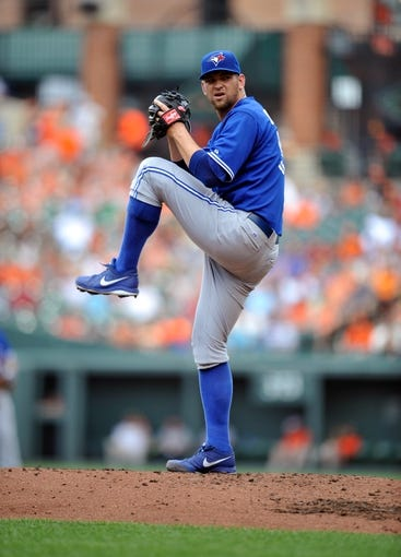 Jul 14, 2013; Baltimore, MD, USA; Toronto Blue Jays starting pitcher Josh Johnson (55) throws in the third inning against the Baltimore Orioles at Oriole Park at Camden Yards. The Orioles defeated the Blue Jays 7-4. Mandatory Credit: Joy R. Absalon-USA TODAY Sports