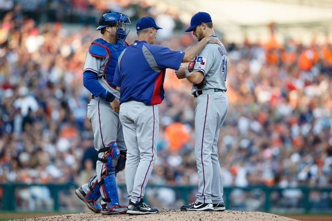 July 12, 2013; Detroit, MI, USA; Texas Rangers pitching coach Mike Maddux (31) talks to starting pitcher Justin Grimm (51) and catcher A.J. Pierzynski (12) against the Detroit Tigers at Comerica Park. Mandatory Credit: Rick Osentoski-USA TODAY Sports