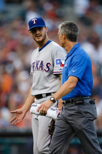 July 12, 2013; Detroit, MI, USA; Texas Rangers starting pitcher Justin Grimm (51) walks off the field with trainer Jamie Reed after getting injured fourth inning against the Detroit Tigers at Comerica Park. Mandatory Credit: Rick Osentoski-USA TODAY Sports
