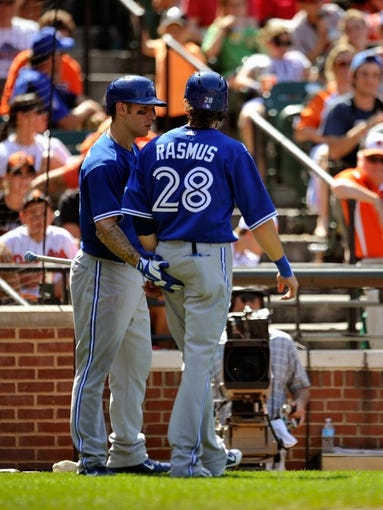 Jul 14, 2013; Baltimore, MD, USA; Toronto Blue Jays center fielder Colby Rasmus (28) is congratulated by Brett Lawrie (13) after scoring on a one-run rbi single by Maicer Izturis (not shown) in the ninth inning against the Baltimore Orioles at Oriole Park at Camden Yards. The Orioles defeated the Blue Jays 7-4. Mandatory Credit: Joy R. Absalon-USA TODAY Sports