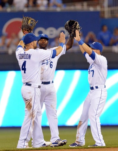 Jul 20, 2013; Kansas City, MO, USA; Kansas City Royals left fielder Alex Gordon (4), center fielder Lorenzo Cain (6), and right fielder David Lough (7) (left to right) celebrate in the outfield after the game against the Detroit Tigers at Kauffman Stadium. The Royals won 6-5. Mandatory Credit: Denny Medley-USA TODAY Sports