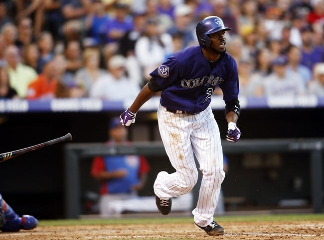 Jul 20, 2013; Denver, CO, USA; Colorado Rockies center fielder Dexter Fowler (24) hits an RBI triple during the fourth inning against the Chicago Cubs at Coors Field. Mandatory Credit: Chris Humphreys-USA TODAY Sports