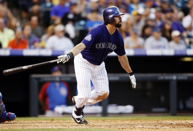 Jul 20, 2013; Denver, CO, USA; Colorado Rockies first baseman Todd Helton (17) hits an RBI single during the fifth inning against the Chicago Cubs at Coors Field. Mandatory Credit: Chris Humphreys-USA TODAY Sports