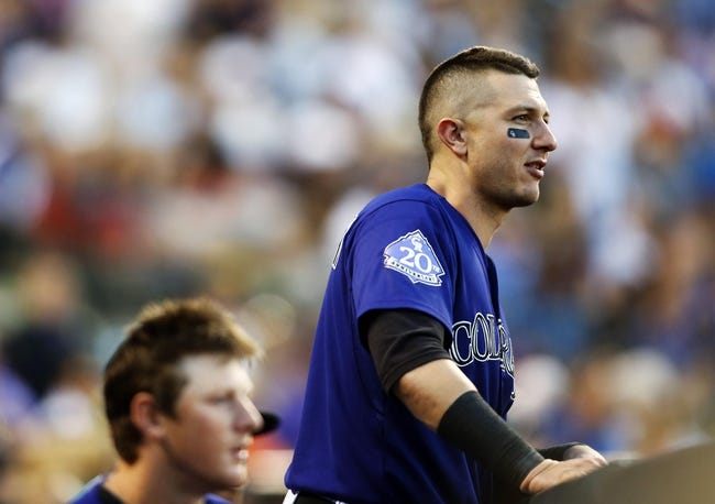 Jul 20, 2013; Denver, CO, USA; Colorado Rockies shortstop Troy Tulowitzki (2) watches from the dugout during the fifth inning against the Chicago Cubs at Coors Field. Mandatory Credit: Chris Humphreys-USA TODAY Sports