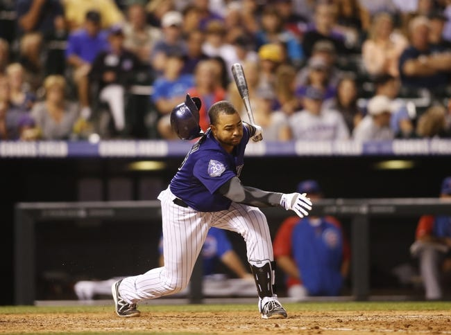 Jul 20, 2013; Denver, CO, USA; Colorado Rockies catcher Wilin Rosario (20) loses his helmet as he strikes out during the seventh inning against the Chicago Cubs at Coors Field. Mandatory Credit: Chris Humphreys-USA TODAY Sports