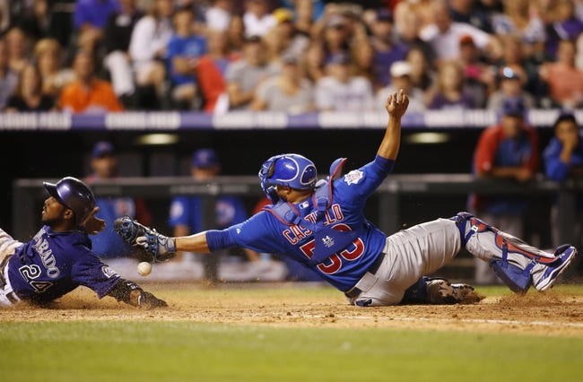 Jul 20, 2013; Denver, CO, USA; Colorado Rockies center fielder Dexter Fowler (24) slides into home plate for a run as Chicago Cubs catcher Welington Castillo (53) can't hold onto the ball during the eighth inning  at Coors Field.  The Rockies won 9-3.  Mandatory Credit: Chris Humphreys-USA TODAY Sports