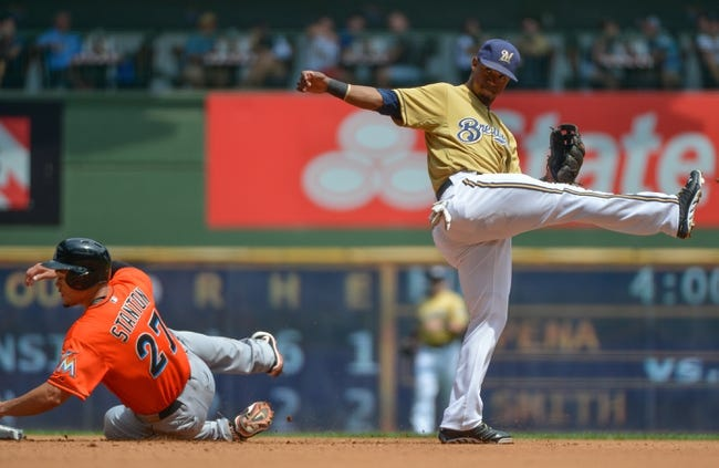 Jul 21, 2013; Milwaukee, WI, USA;  Milwaukee Brewers shortstop Jean Segura (right) reacts after forcing out Miami Marlins right fielder Giancarlo Stanton (left) and completing a double play in the 4th inning at Miller Park. Mandatory Credit: Benny Sieu-USA TODAY Sports