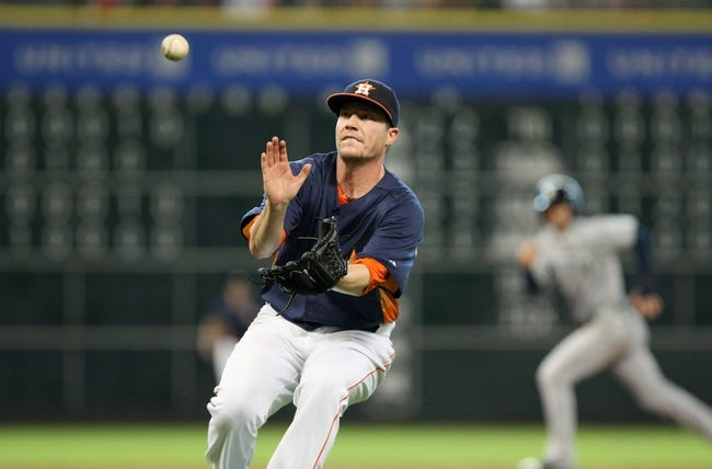 Jul 21, 2013; Houston, TX, USA; Houston Astros pitcher Lucas Harrell (64) fields a ground ball during the sixth inning against the Seattle Mariners at Minute Maid Park. Mandatory Credit: Troy Taormina-USA TODAY Sports