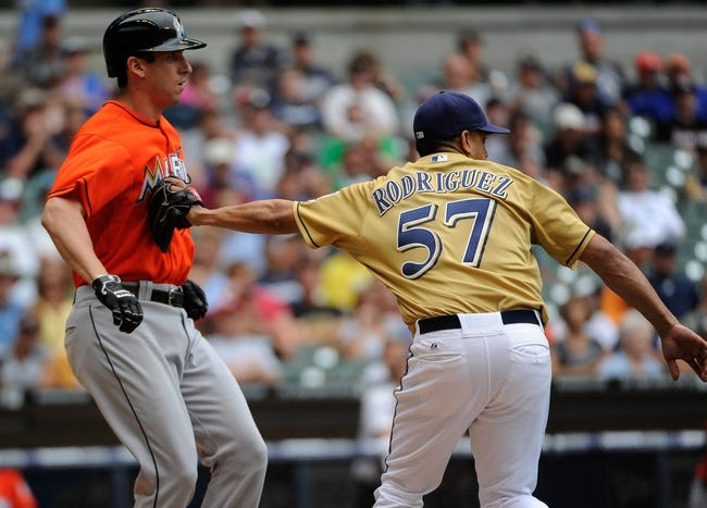 Jul 21, 2013; Milwaukee, WI, USA;  Milwaukee Brewers pitcher Francisco Rodriguez (right) tags out Miami Marlins third baseman Ed Lucas (left) after a sacrifice bunt in the 9th inning at Miller Park. Mandatory Credit: Benny Sieu-USA TODAY Sports