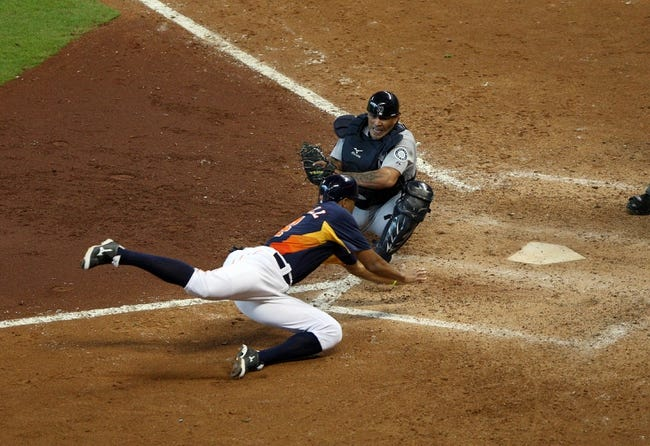 Jul 21, 2013; Houston, TX, USA; Houston Astros center fielder Justin Maxwell (44) slides safely as Seattle Mariners catcher Henry Blanco (33) attempts to make the tag during the ninth inning at Minute Maid Park. Mandatory Credit: Troy Taormina-USA TODAY Sports