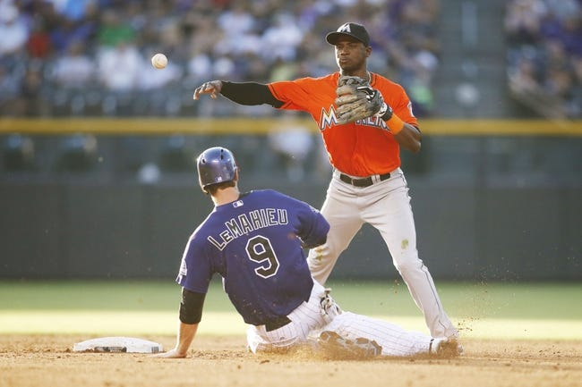 Jul 22, 2013; Denver, CO, USA; Miami Marlins shortstop Adeiny Hechavarria (right) forces out Colorado Rockies second baseman DJ LeMahieu (9) at second base as he turns the double during the third inning at Coors Field. Mandatory Credit: Chris Humphreys-USA TODAY Sports
