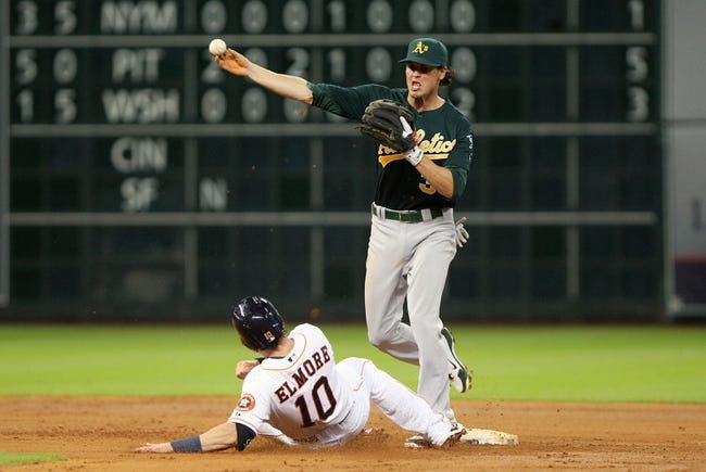 Jul 22, 2013; Houston, TX, USA; Houston Astros left fielder Jake Elmore (10) slides as Oakland Athletics second baseman Grant Green (35) throws to first base to complete a double play during the fourth inning at Minute Maid Park. Mandatory Credit: Troy Taormina-USA TODAY Sports