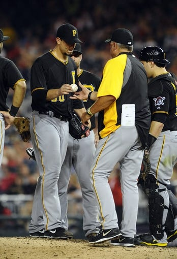 Jul 22, 2013; Washington, DC, USA; Pittsburgh Pirates starting pitcher Charlie Morton (50) hands the ball to manager Clint Hurdle after being removed from the game during the seventh inning against the Washington Nationals at Nationals Park. Mandatory Credit: Brad Mills-USA TODAY Sports