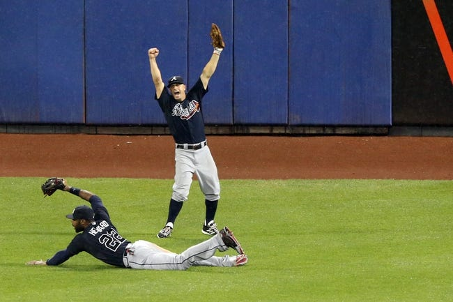 Jul 22, 2013; New York, NY, USA;  Atlanta Braves right fielder Jason Heyward (22) fields a ball for the final out as left fielder Reed Johnson (7) begins to celebrate the win against the New York Mets at Citi Field.  Atlanta Braves won 2-1.  Credit: Anthony Gruppuso-USA TODAY Sports