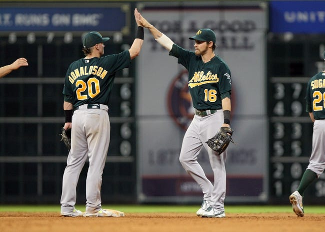 Jul 22, 2013; Houston, TX, USA; Oakland Athletics third baseman Josh Donaldson (20) and right fielder Josh Reddick (16) celebrate after defeating the Houston Astros 4-3 at Minute Maid Park. Mandatory Credit: Troy Taormina-USA TODAY Sports