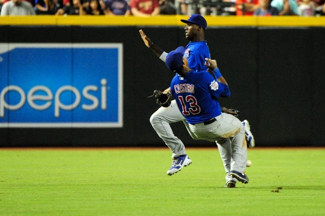Jul 22, 2013; Phoenix, AZ, USA;  Chicago Cubs shortstop Starlin Castro (13) and shortstop Junior Lake (21) collide and miss catching the ball during the sixth inning against the Arizona Diamondbacks at Chase Field. Mandatory Credit: Matt Kartozian-USA TODAY Sports