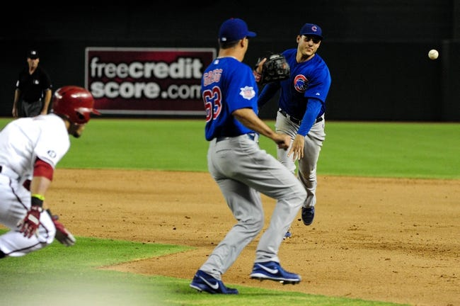 Jul 22, 2013; Phoenix, AZ, USA;  Chicago Cubs first baseman Anthony Rizzo (44) throws the ball to relief pitcher Kevin Gregg (63) as Arizona Diamondbacks right fielder Gerardo Parra (8) runs during the ninth inning at Chase Field. Mandatory Credit: Matt Kartozian-USA TODAY Sports