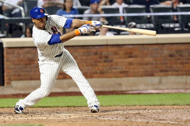 Jul 23, 2013; New York, NY, USA;  New York Mets center fielder Juan Lagares (12) hits a sacrifice fly allowing a runner to score during the sixth inning against the Atlanta Braves at Citi Field.  Mandatory Credit: Anthony Gruppuso-USA TODAY Sports