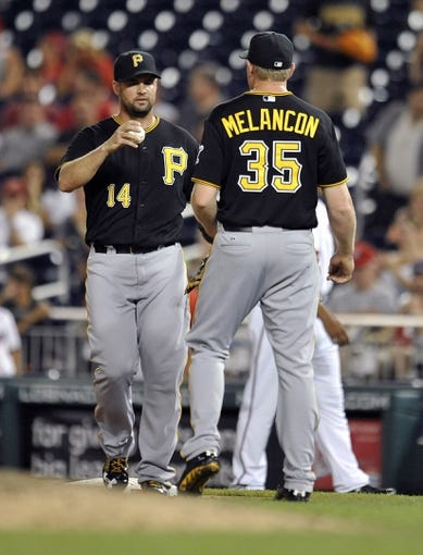 Jul 23, 2013; Washington, DC, USA; Pittsburgh Pirates first baseman Gaby Sanchez (14) hands the game ball to pitcher Mark Melancon (35) after a game against the Washington Nationals at Nationals Park. The Pirates defeated the Nationals 5-1. Mandatory Credit: Joy R. Absalon-USA TODAY Sports
