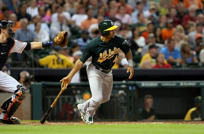 Jul 23, 2013; Houston, TX, USA; Oakland Athletics center fielder Coco Crisp (4) gets a single during the fifth inning against the Houston Astros at Minute Maid Park. Mandatory Credit: Troy Taormina-USA TODAY Sports
