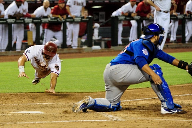 Jul 23, 2013; Phoenix, AZ, USA; Arizona Diamondbacks left fielder Adam Eaton (left) slides to score on a hit by center fielder A.J. Pollock (not pictured) as Chicago Cubs catcher Dioner Navarro (30) waits for the ball during the sixth inning at Chase Field. Mandatory Credit: Matt Kartozian-USA TODAY Sports