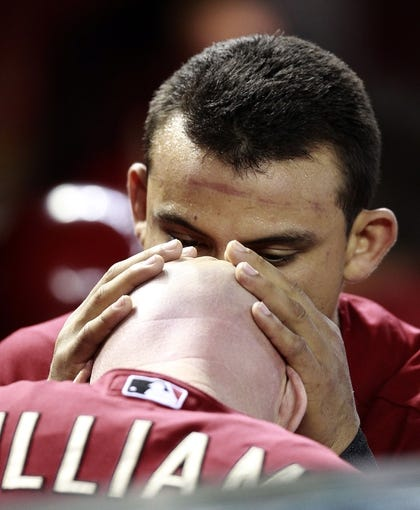 Jul 24, 2013; Phoenix, AZ, USA; Arizona Diamondbacks right fielder Gerardo Parra (8) kisses third base coach Matt Williams (9) before a baseball game against the Chicago Cubs at Chase Field. Mandatory Credit: Rick Scuteri-USA TODAY Sports
