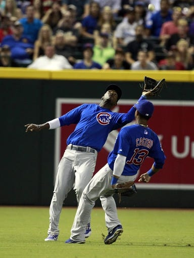 Jul 24, 2013; Phoenix, AZ, USA; Chicago Cubs center fielder Junior Lake (21) makes the catch while avoiding shortstop Starlin Castro (13) in the fifth inning during a baseball game against the Arizona Diamondbacks at Chase Field. Mandatory Credit: Rick Scuteri-USA TODAY Sports