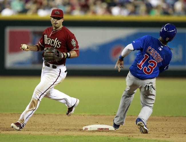 Jul 24, 2013; Phoenix, AZ, USA; Arizona Diamondbacks second baseman Martin Prado (14) turns a double play over Chicago Cubs shortstop Starlin Castro (13) in the eighth inning during a baseball game at Chase Field. Mandatory Credit: Rick Scuteri-USA TODAY Sports