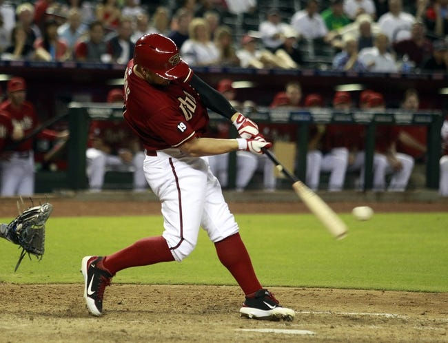 Jul 24, 2013; Phoenix, AZ, USA; Arizona Diamondbacks right fielder Cody Ross (7) hits an RBI sacrifice fly and ties the game in the ninth inning during a baseball game against the Chicago Cubs at Chase Field. Mandatory Credit: Rick Scuteri-USA TODAY Sports