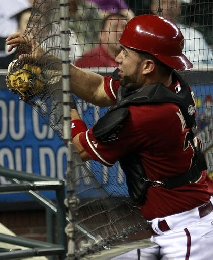 Jul 24, 2013; Phoenix, AZ, USA; Arizona Diamondbacks catcher Wil Nieves (27) tries to catch the ball against the screen in the 12th inning during a baseball game against the Chicago Cubs at Chase Field. Mandatory Credit: Rick Scuteri-USA TODAY Sports