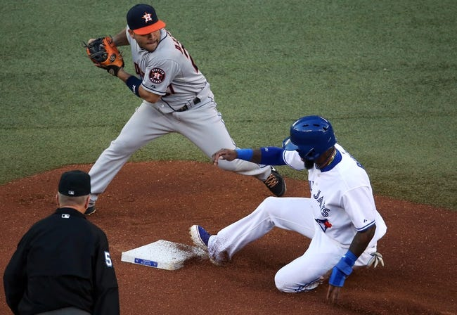 Jul 25, 2013; Toronto, Ontario, CAN; Houston Astros second baseman Jose Altuve (27) turns a double play in the first inning as Toronto Blue Jays shortstop Jose Reyes #7 slides at Rogers Centre. Mandatory Credit: Tom Szczerbowski-USA TODAY Sports