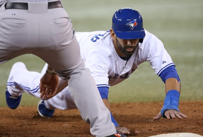 Jul 25, 2013; Toronto, Ontario, CAN; Toronto Blue Jays right fielder Jose Bautista (19) dives back to first base on a pick-off attempt against the Houston Astros at Rogers Centre. The Blue Jays beat the Astros 4-0. Mandatory Credit: Tom Szczerbowski-USA TODAY Sports