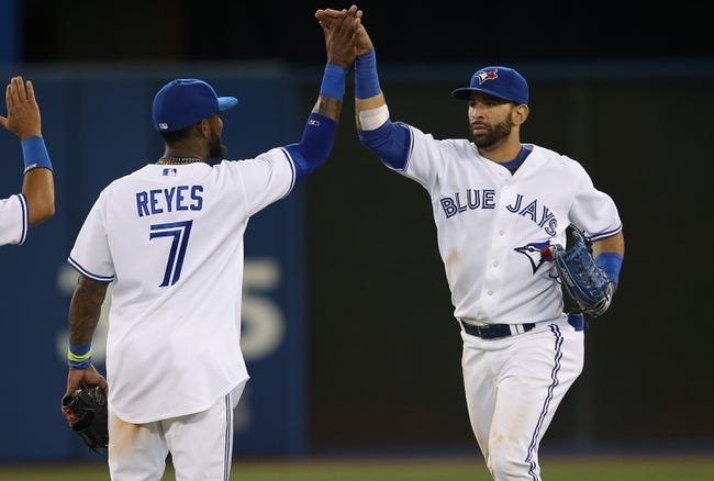 Jul 25, 2013; Toronto, Ontario, CAN; Toronto Blue Jays right fielder Jose Bautista (19) celebrates their victory with shortstop Jose Reyes (7) against the Houston Astros at Rogers Centre. The Blue Jays beat the Astros 4-0. Mandatory Credit: Tom Szczerbowski-USA TODAY Sports