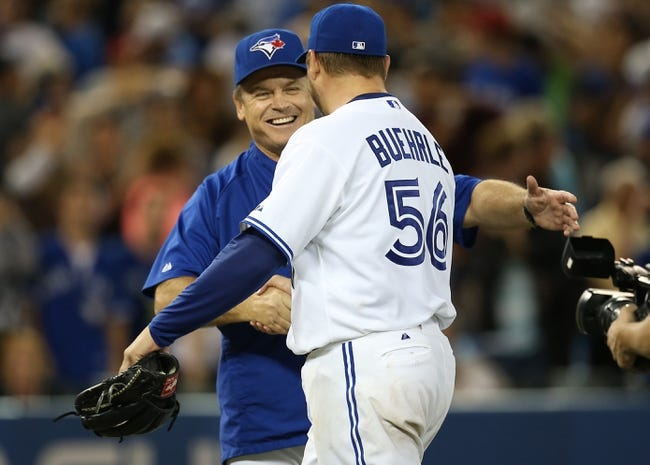 Jul 25, 2013; Toronto, Ontario, CAN; Toronto Blue Jays starting pitcher Mark Buehrle (56) is congratulated by manager John Gibbons (5) after his complete-game victory against the Houston Astros at Rogers Centre. The Blue Jays beat the Astros 4-0. Mandatory Credit: Tom Szczerbowski-USA TODAY Sports